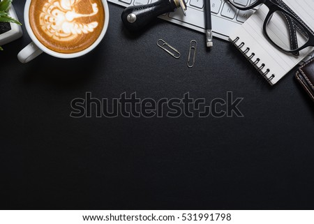 Cup of coffee, top view at the studio,Office leather desk table with coffee and supplies. Top view with copy space