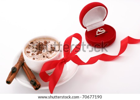 cup of coffee with a red ribbon and a ring