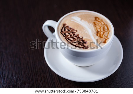 Cup of coffee with a white leaf drawing, and other barista drawings #733848781