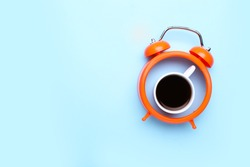 Cup of coffee with alarm clock on color background