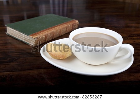 Cup of coffee with an apple cake on saucer next to book on for Apple coffee table book
