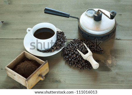 cup of coffee with bean and old coffee roaster, wooden table