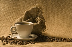 Cup of coffee with beans and sack over brown burlap background