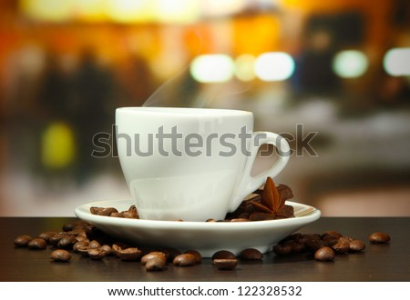cup of coffee with beans on table in cafe