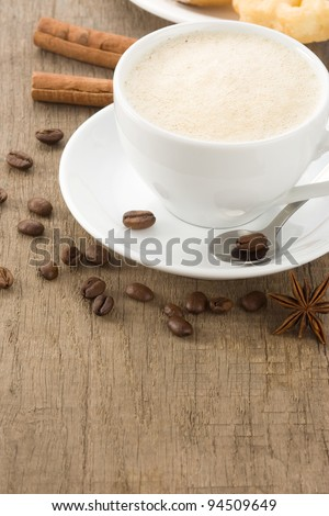 cup of coffee with beans on wood