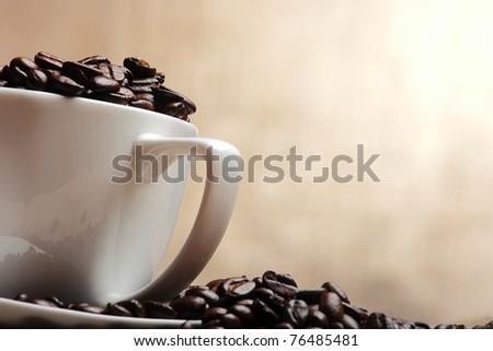 cup of coffee with beans on yellow background