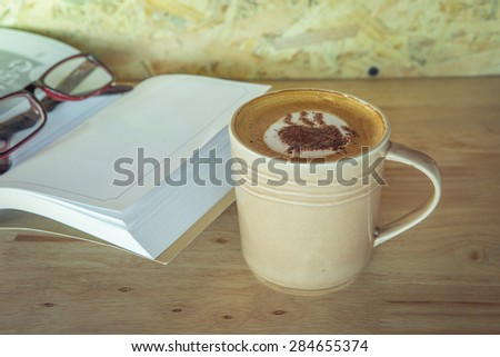 Cup of coffee with book and grass on table