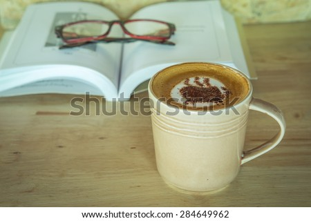 Cup of coffee with book and grass on table , vintage style image