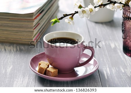 Cup of coffee  with branches of blooming cherry on wooden background