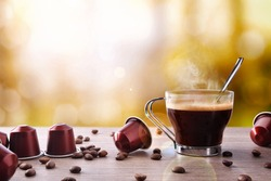 Cup of coffee with capsules and beans and local background. Front view