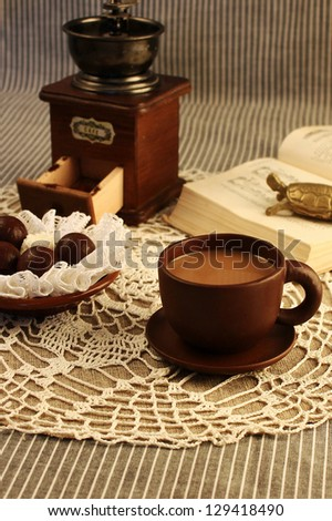 cup of coffee with chocolate and coffee grinder