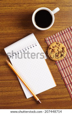 Cup of coffee with chocolate cookies and opened notepad on desk