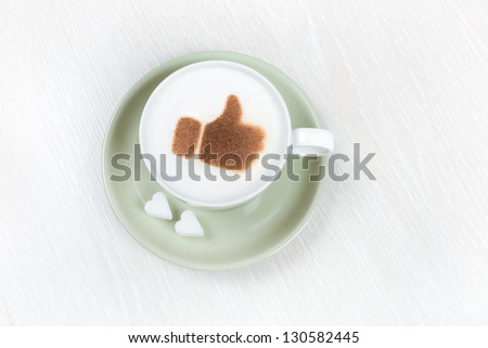 Cup of coffee with chocolate thumbs up and heart shaped sugar