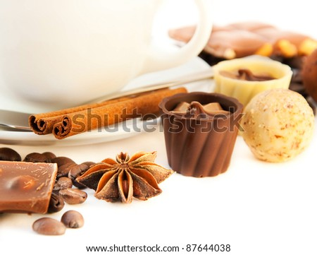 Cup of coffee with chocolates, coffee grains with cinnamon and an anise - stock photo