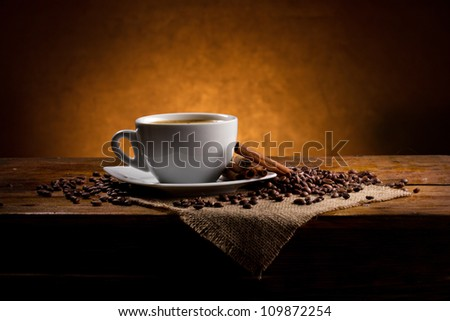 cup of coffee with cinnamon sticks and coffee beans on dark background