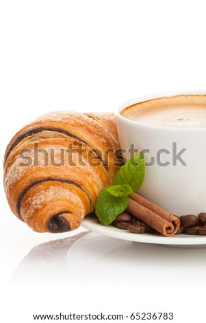 Cup of coffee with coffee beans, cinnamon sticks and chocolate croissant on white background
