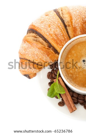 Cup of coffee with coffee beans, cinnamon sticks and chocolate croissant upper view