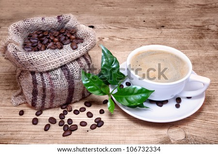 Cup of coffee with coffee beans in a beautiful brown bag, green branch of a coffee plant