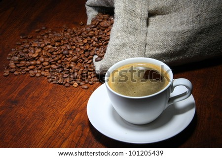 Cup of coffee with coffee beans on a beautiful wooden background.