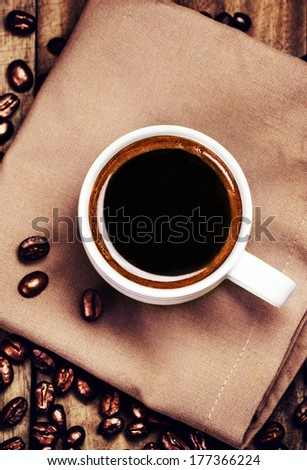 Cup of coffee with coffee beans on  brown napkin on wooden background. White Cup of espresso, top view.
