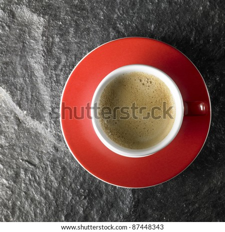 cup of coffee with crema, seen from above with red saucer on dark stone surface