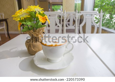 cup of coffee with flower  on table in cafe