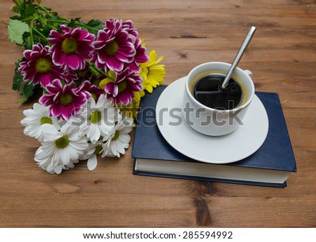 Cup of coffee with flowers and book on old wooden table