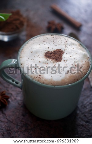 Cup of coffee with heart of cocoa, cinnamon and spring flowers on dark stone background, fresh morning, breakfast for Valentines day, selective focus #696331909