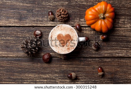 Cup of coffee with heart shape and pine cone with acorn and pumpkin on wooden background