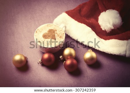 Cup of coffee with heart shape near Santas hat and christmas bubbles. Photo in old color image style. #307242359
