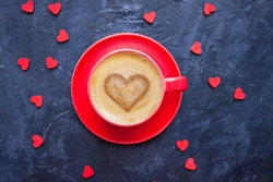 Cup of coffee with heart shape on dark blue background for Valentine's Day greeting card. Top view.