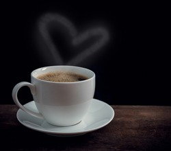 Cup of coffee with heart shape smoke on old wooden table