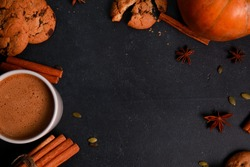 Cup of coffee with milk and foam, spices, orange pumpkins, seeds, cookies on black table. Autumn drink concept. Fall, spicy latte, home, pastry, thanksgiving, coffee shop menu, top view
