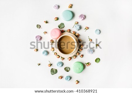 Cup of coffee with milk and macarons on white background. Flat lay, top view
