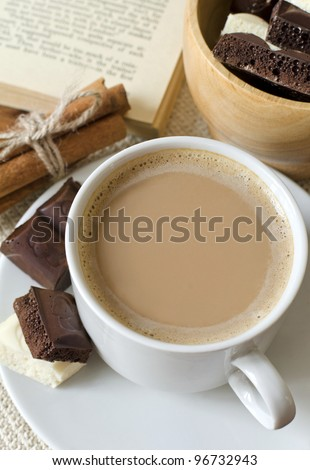 Cup of coffee with milk, chocolate and the opened book