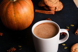 Cup of coffee with milk foam, spices, orange pumpkin, seeds, cookies on black table. Autumn drink concept. Fall, spicy latte, home, pastry, thanksgiving, coffee shop menu, closeup