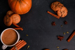 Cup of coffee with milk foam, spices, orange pumpkins, seeds, cookies on black table. Autumn drink concept. Fall, spicy latte, home, pastry, thanksgiving, coffee shop menu, top view