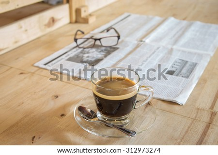 Cup of coffee with newspaper and glasses on table