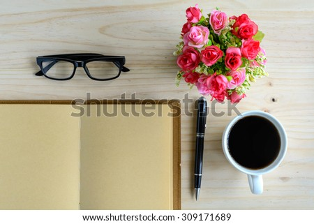Cup of coffee with notebook and flower on desk, workplace