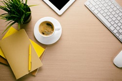 Cup of coffee with office tools on wooden background
