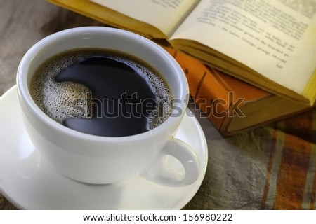 Cup of coffee with old books in the background