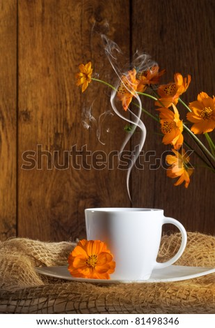 Cup of coffee with orange flowers on wooden background