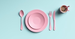 Cup of coffee with pink fork, knife and spoon, top view. Clear ceramic dishware with set cutlery design. Empty green table ware for lunch or dinner in cafe. copyspace for your individual text.