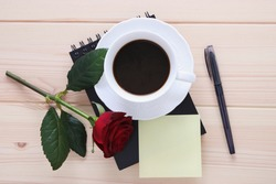 Cup of coffee with red rose and pen with place for the text at the wooden background, coffee break, romantic and poetic theme