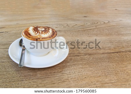 cup of coffee with rose coffee art on top