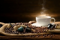 Cup of coffee with smoke and coffee beans and coffee capsules on burlap sack on old wooden background