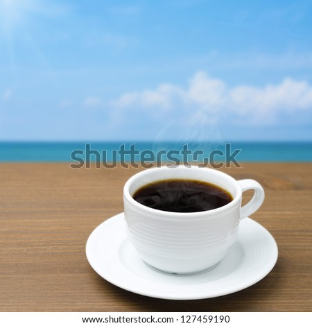 cup of coffee with steam on a wooden table on a background of blue sky