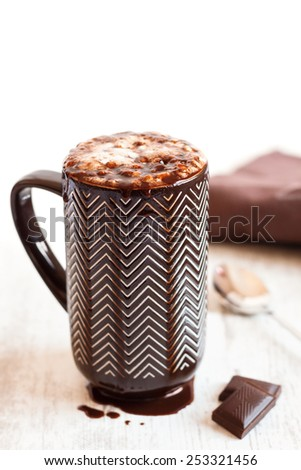 Cup of coffee with whipped cream and melted chocolate on white background