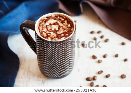 Cup of coffee with whipped cream and melted chocolate on white background with towel