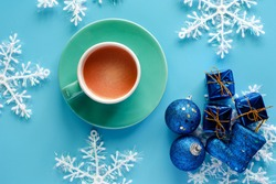 Cup of coffee with Xmas snowflake, gift box, glitter balls and boot ornaments on blue background for drinks and beverage on Christmas day and holidays concept